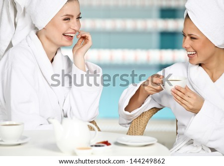 Two beautiful young girls having fun at spa salon