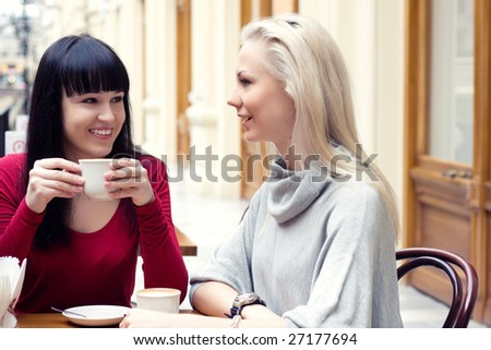 Two beautiful young girls sitting by the table in cafe