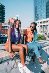 Two beautiful young sisters outdoor having fun laughing - positive, emancipation, woman power concept