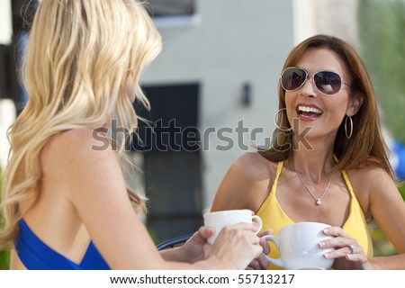 Two beautiful young woman outside at a city cafe laughing and drinking coffee
