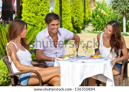 Two beautiful young women and a handsome male friend enjoying a meal in a tropical garden seated at a table together laughing and smiling