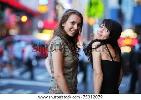 Two beautiful young women at Times Square in New York City. Shallow DOF.