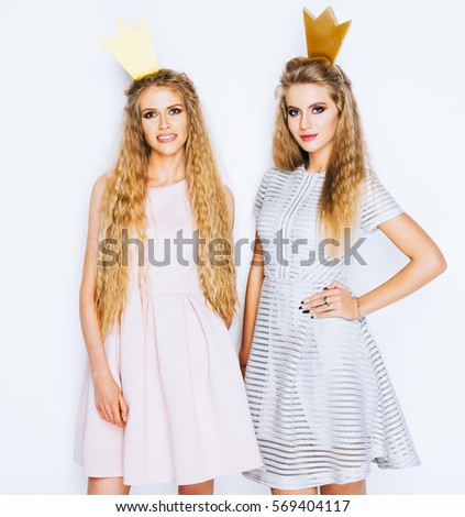 Two beautiful young women celebrate party and drinking cocktails on white background. Best friends wearing stylish evening dress, gold crown on head . Princess and Queen.