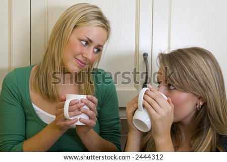 Two beautiful young women chatting over a warm drink. - stock photo