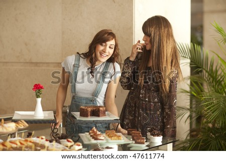 Two beautiful young women enjoying a dessert buffet, smiling, palm tree in the background.