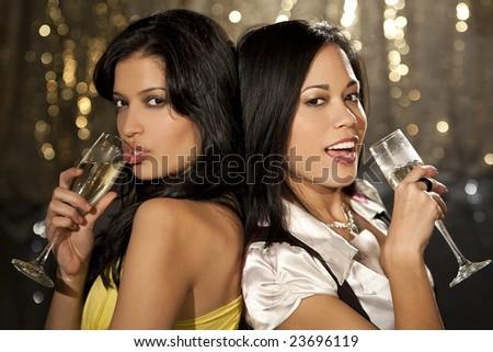 Two beautiful young women enjoying champagne in a nightclub