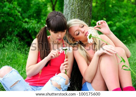 Two beautiful young women friends having fun outdoor.