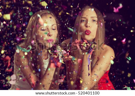 Two beautiful young women having fun at a Christmas party, blowing away confetti and sending kisses. Focus on the girl on the left #520401100