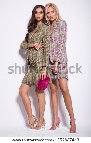 Two beautiful young women in nice clothes, high heels, posing in a studio. Fashion glamour photo.