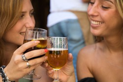 Two beautiful young women toasting with two glasses in a bar. The girls smile as they toast with beer. Concept of friendship and happiness