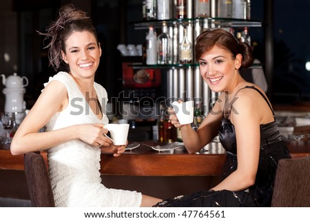 Two beautiful young women with great smile and hairstyle sitting at a bar, drinking coffee.