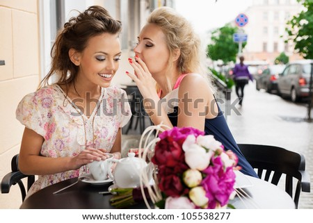 Two beautiful young women with great smile sitting at a bar, drinking tea and coffee.