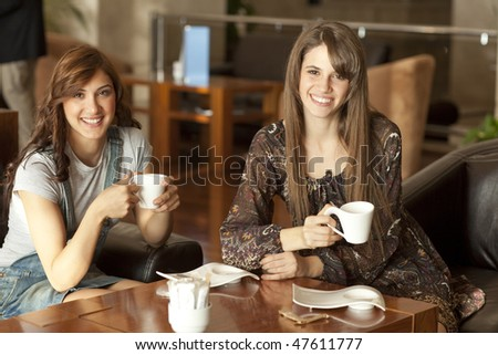 Two beautiful young women with great teeth enjoying their lunch break, drinking coffee, smiling to the camera