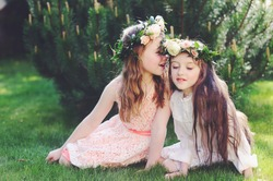 Two beauty kid girls in elegant dresses with flowers wreath on the heads sitting on the lawn and speaking