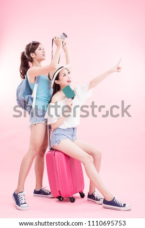 two beauty woman take camera and passport smile happily on the pink background