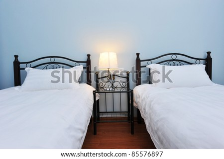 Two beds bedroom with bedside table and lamp.
