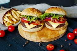 Two beef burgers, fries potatoes and cherry tomatoes on dark wooden table