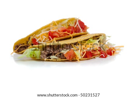 Two beef tacos on corn torillas with beef, lettuce, tomatoes and cheese on a white background with copy space