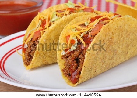 Two beef tacos with lettuce, tomato, cheese and sauce