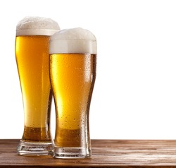 Two beer glasses on a wooden table. Isolated on a white background.