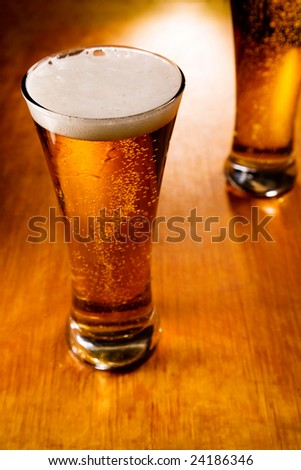 Two beer glasses on wood background, selective focus