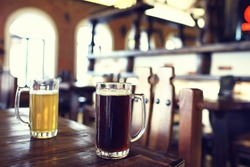 two beer mugs in a Czech beer restaurant / light and dark beer in large mugs traditional Prague pub