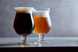 Two beers in belgian glasses. Brown beer in the front, off focus blonde beer in the back, over concrete gray background.