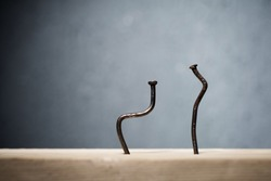 Two bent nails driven into a board. Concept stoop, sciatica and degenerative disc disease - image