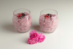 Two berry pink smoothies are available in clear textured glasses. The smoothie contains red and black currant berries. There are three pink carnations between the glasses.