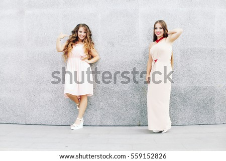 Two best friends embracing over gray wall. Young women having fun together. Sisters at the prom with gorgeous long curly hair. Professional make-up and hairstyle.