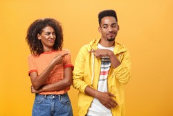 Two best friends fooling around having fun pointing at each other with cute joyful smile as if blaming each other playfully. Cute female looking at boyfriend standing together over orange wall