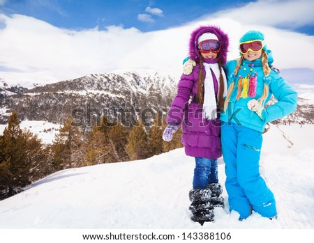 Two best friends girls spending vacation on the ski resort in mountains