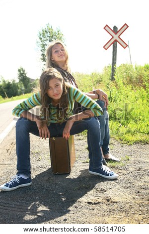 stock photo : Two best friends teenager girls sit on a old luggage with a ...