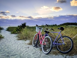 Two bicycles in the sand at sunset at Fort Myers beach in Florida