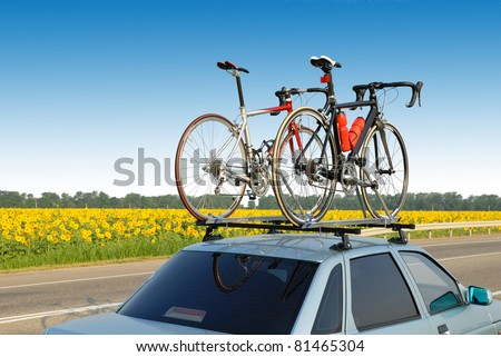 two bicycles mounted on roof of car against sky