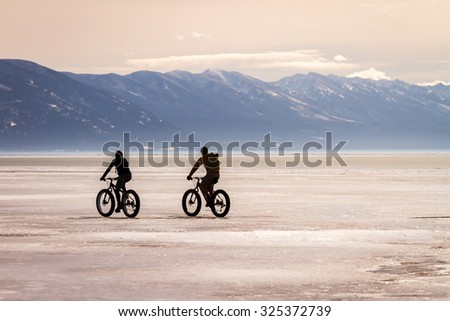 two bicyclists ride fat tire...