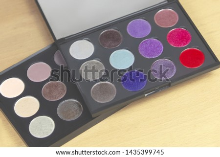 Two big eye shadow palettes of many colors shades in neutral. taupe and bright lilac, violet and red tones, one above another one. Indoors, light wooden background, close up, copy space. #1435399745