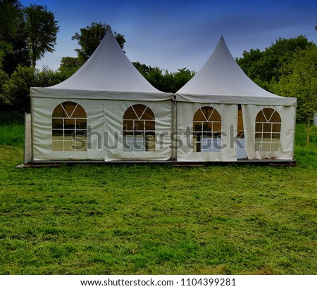 Two big white tents for events in the woods on a festival meadow #1104399281
