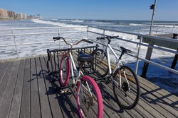 Two bikes locked in a bicycle rack on a boardwalk over a beach with sand and ocean in the background. One bicycle is pink.