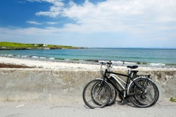 Two bikes near sandy beach on Inishmore, the largest of the Aran Islands in Galway Bay, Ireland. Famous for its strong Irish culture, loyalty to the Irish language, and a wealth of ancient sites.