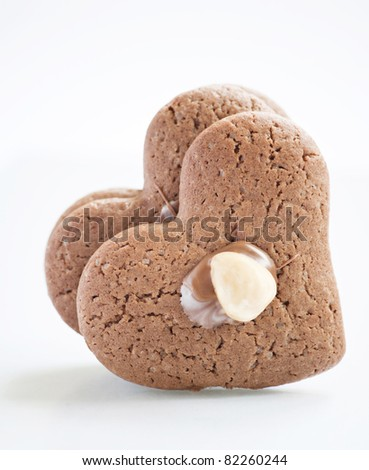 Two biscuits in shape of heart over white background