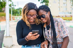 two black african girl friends looking at a mobile phone and smiling outdoors