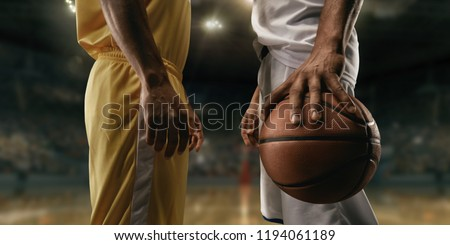 Two black basketball players on big professional arena before the game. Two teams. Players collided face to face. Player holds a ball. Close up