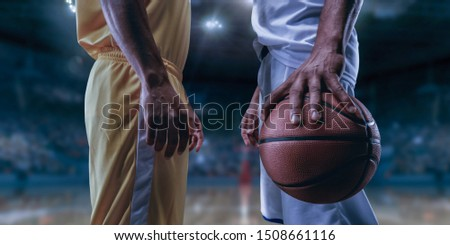 Two black basketball players on big professional arena before the game. Two teams. Players collided face to face. Player holds a ball.