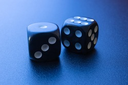 Two black dice on a black matte background with side blue lighting. One and six.