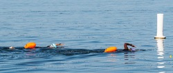 Two black female triatholon swimmers with orange flotation devices for safety are about to pass a buoy while training in the sea.