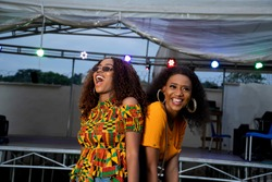 two black girls dancing at a concert held at night