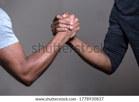 Two black hands locked in a clasp, symbol of friendship, brotherhood, help, cooperation