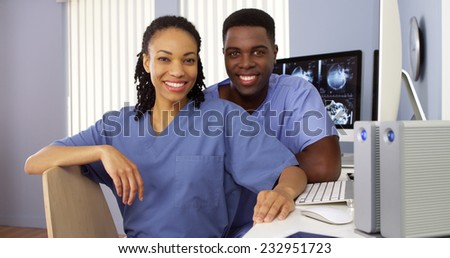 Two Black nurses in nurses station sitting at computer