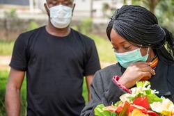two black people mourning lost ones to coronavirus, wearing face masks, physical distancing